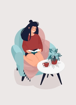 Woman is reading a book in a comfortable chair