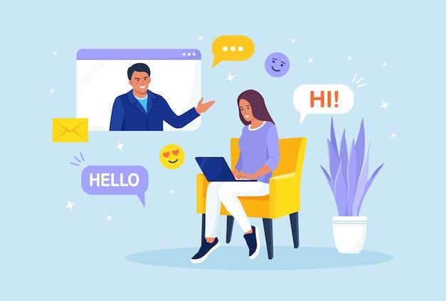 Женщина сидит на кресле и использует ноутбук для видеозвонка с парнем или коллегой. друзья разговаривают в сети. онлайн-образование и электронное обучение. социальные сети или приложение для знакомств и виртуальные отношения