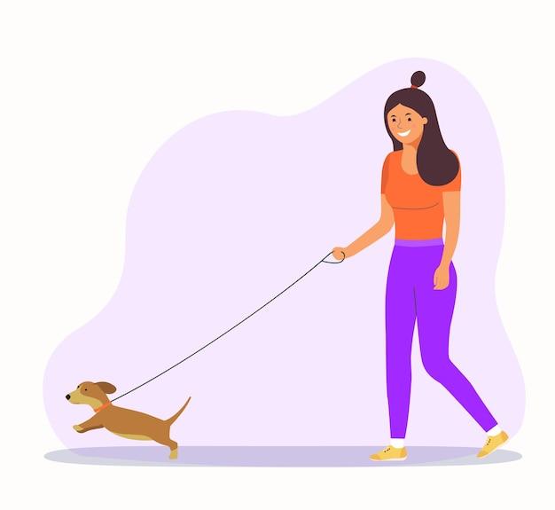 여자는 강아지와 함께 걷고있다.