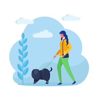 女性は犬を連れて歩いています。幸せな女の子はペットと遊ぶ。背景に鎖の子犬。