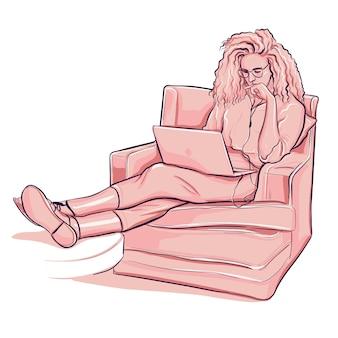 女性は肘掛け椅子に座ってラップトップで働いています