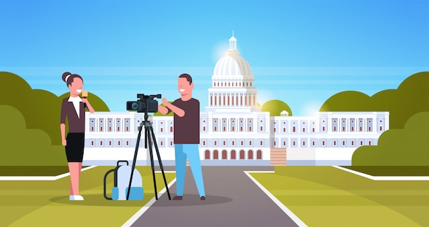 Woman journalist with reporter man presenting live news operator using video camera on tripod recording correspondent movie making concept horizontal senate white house washington ds background