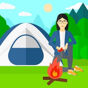 Женщина разжигает огонь.