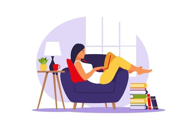 女性は肘掛け椅子にラップトップで横たわっています。仕事、勉強、教育、在宅勤務の概念図。