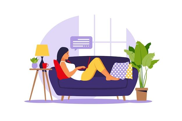 女性はソファの上にラップトップで横たわっています。仕事、勉強、教育、在宅勤務の概念図。平らな。ベクトルイラスト。