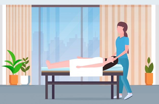 Woman lying on massage bed  masseuse doing healing treatment massaging injured patient manual physical therapy rehabilitation concept modern clinic spa salon interior full length