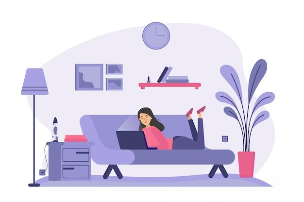 Женщина, лежа на диване и с помощью ноутбука