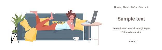 Женщина лежит на диване с помощью ноутбука онлайн-общение социальные сети удаленная работа концепция самоизоляции горизонтальная копия пространства