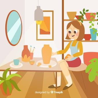 彼女の机で陶器を作る女性