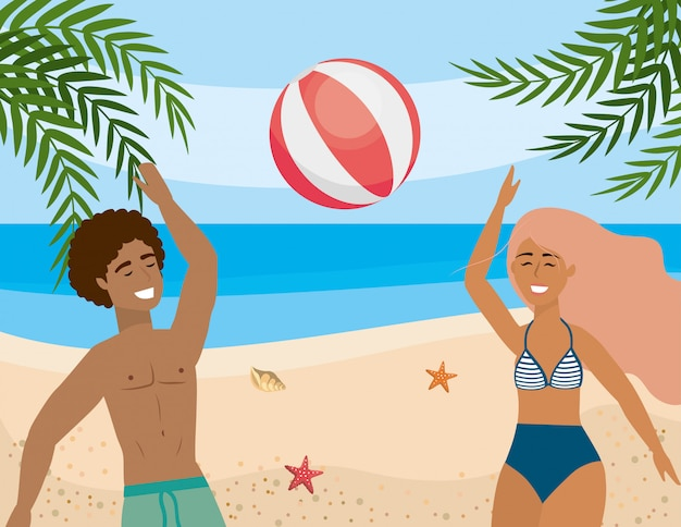 Woman and man playing with beach ball and in the sand