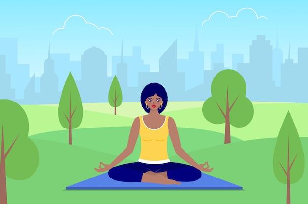 Женщина медитирует, сидя на природе.
