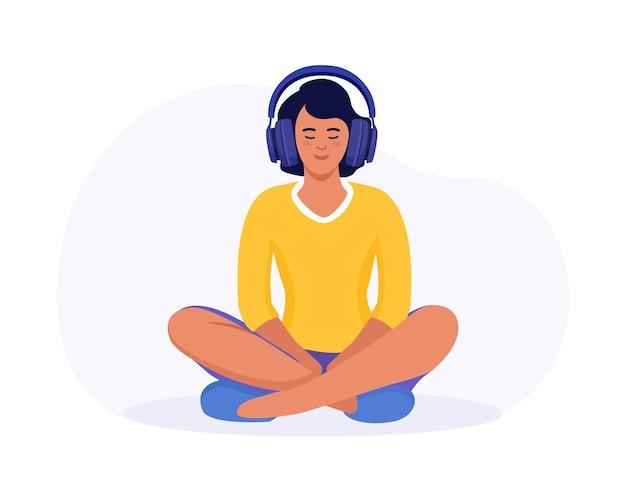蓮華座で瞑想している女性。ガイド付き瞑想を練習しているヘッドフォンを持つ少女。ポッドキャスト。オンライントレーニング、ラジオ。ヘッドフォンを持ったキャラクターは音楽を聴き、イヤホンで歌を楽しみます