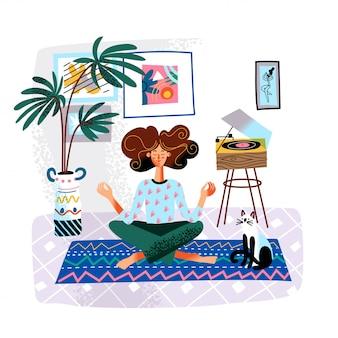 Женщина медитирует, сидя в позе лотоса с кошкой, повседневная жизнь рутина
