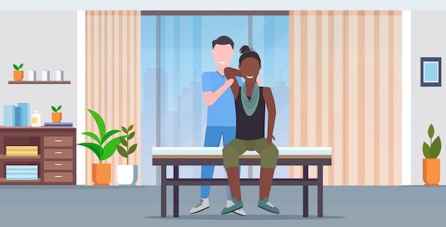 여자 환자 치유 치료 마사지 환자의 몸 수동 스포츠 물리 치료 개념 현대 클리닉 병실 인테리어 가로 하 고 테이블 안마사에 앉아