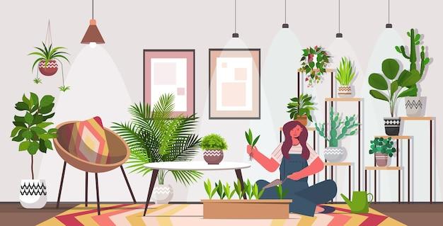 ポットに観葉植物を植える女性主婦彼女の植物の世話をするリビングルームのインテリア水平