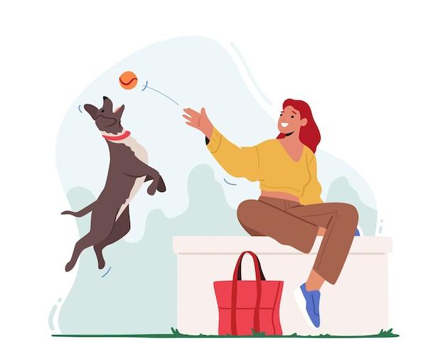 Женщина играет в мяч с домашним животным, проводя время в летнем городском парке