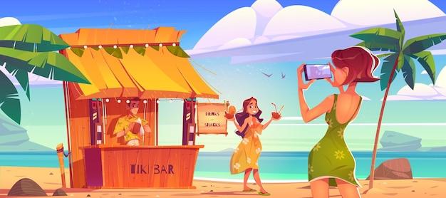바텐더와 티키 오두막 바 근처 손에 칵테일과 함께 사진 촬영을 위해 해변에서 포즈를 취하는 여자