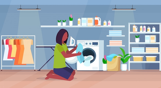 Woman putting dirty clothes into washing machine african american housewife doing housework modern laundry room interior cartoon character full length flat horizontal