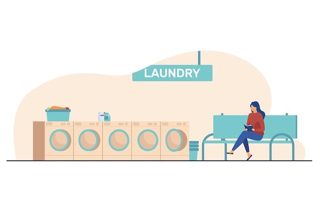 本を読んで洗濯物を待っている女性。