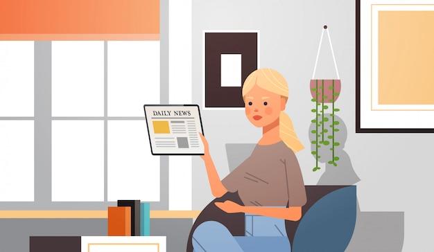 Женщина читает ежедневные новости на экране планшетного пк