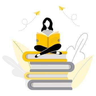 大きな本の概念図のスタックに座って読んでいる女性