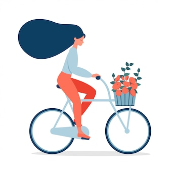 Woman ride on bicycle with bouquet in basket