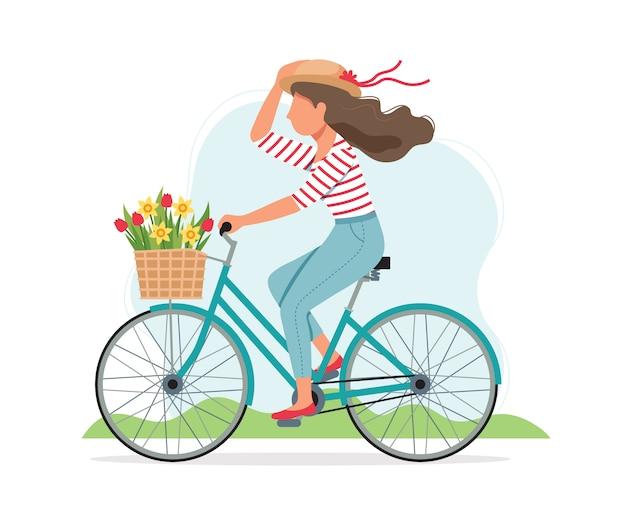 바구니에 꽃과 함께 봄에서 자전거를 타는 여자.