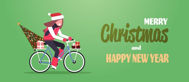 Woman riding bike with fir tree gift box for christmas