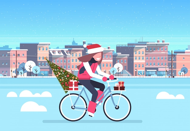 Woman riding bike with fir tree gift box over city street buildings cityscape