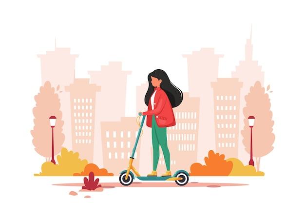 秋に電動キックスクーターに乗る女性。エコ輸送のコンセプト。