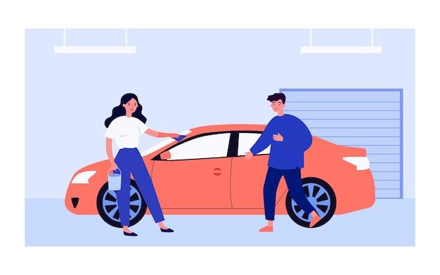 ガレージで布で車をこする女性