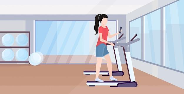 여자 운동 디지털 가제트 중독 개념 현대 체육관 스튜디오 인테리어 전체 길이 가로 훈련하는 동안 스마트 폰을 사용하여 디딜 방아 소녀에서 실행