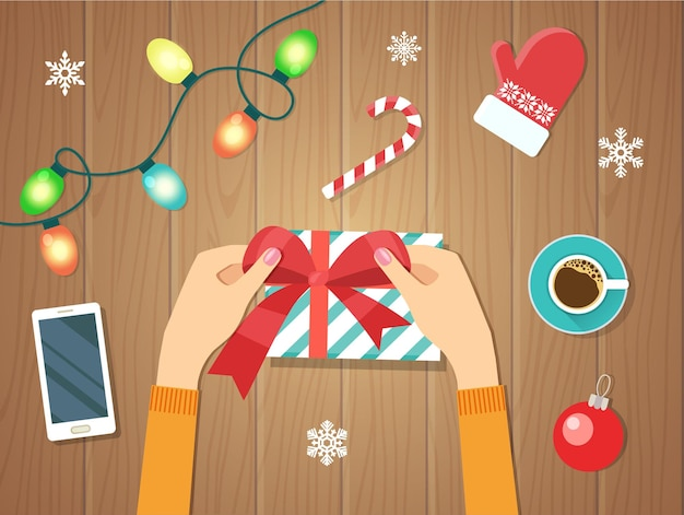 女性の手は赤いリボンで紙に包まれたクリスマスの休日の手作りのプレゼントを与えます。フラットベクトルイラスト。