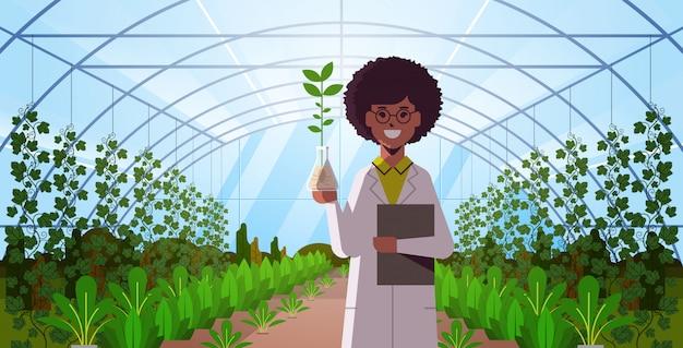 女性の科学者が試験管の植物サンプルを調べる現代ガラス温室インテリア研究