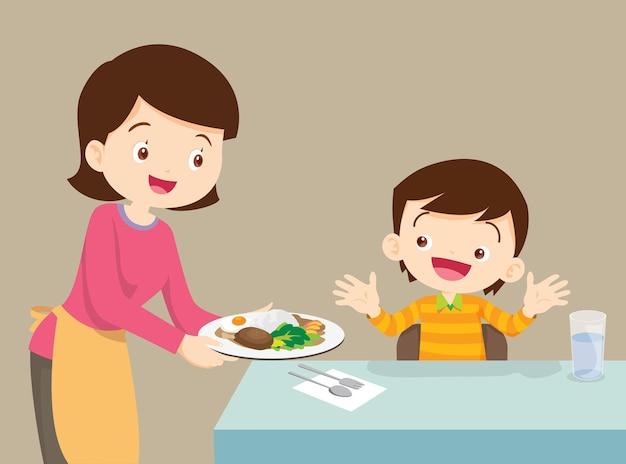 Женщина, подающая еду ребенку