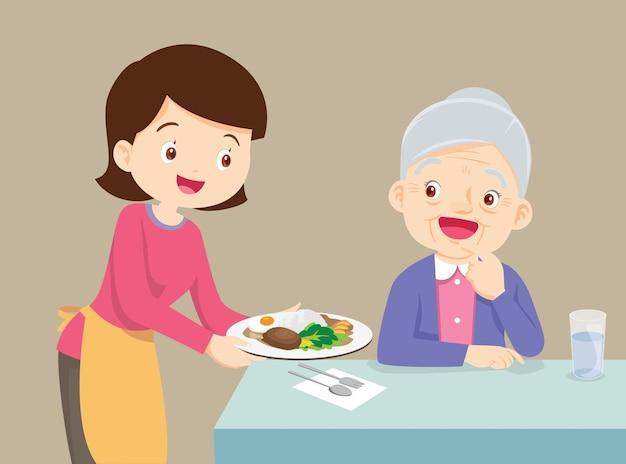 노인 여성에게 음식을 제공하는 여성