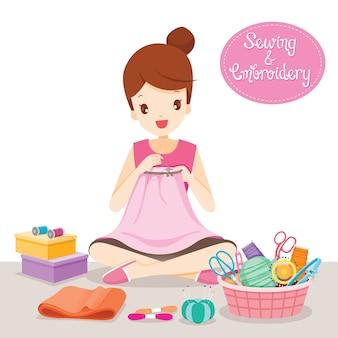 Женщина шьет одежду в пяльцах вручную