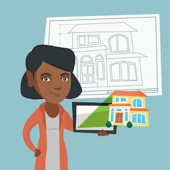 家の写真とデジタルタブレットを示す女性。
