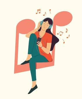 여자는 큰 음표 기호에 앉아 스마트 폰에서 노래를 듣습니다.