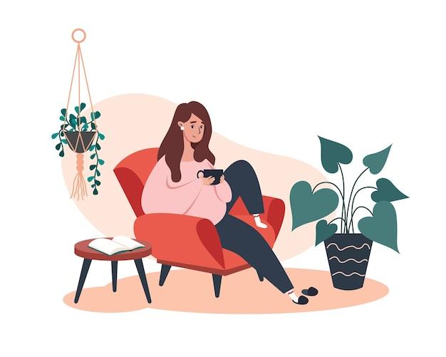 Женщина сидит и отдыхает на кресле с кофе, отдыхает дома Premium векторы