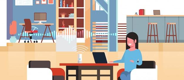 Женщина сидя на рабочем месте с ноутбуком используя интеллектуальный умный динамик с распознаванием голоса концепция искусственного интеллекта помощь интерьер рабочее пространство квартира горизонтальный портрет