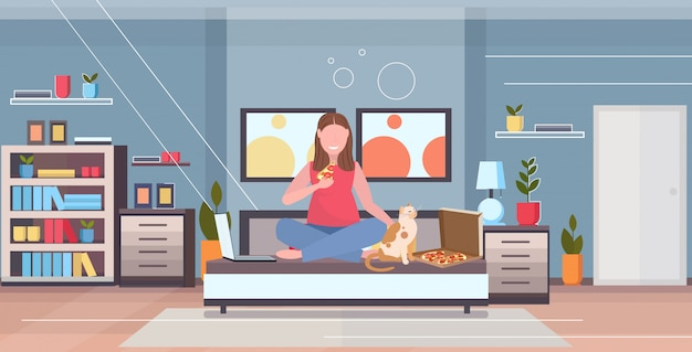 Woman sitting on bed with cat overweight girl eating pizza using laptop unhealthy nutrition obesity concept modern apartment bedroom interior flat full length horizontal