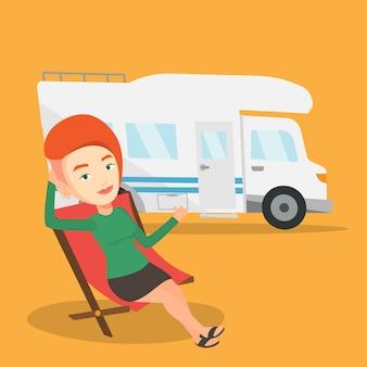 Woman sitting in chair in front of camper van.
