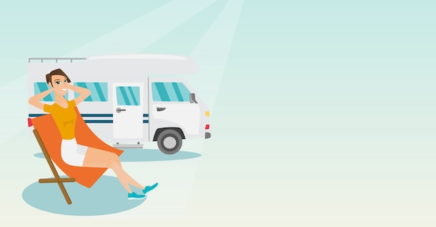 Woman sitting in a chair in front of camper van.