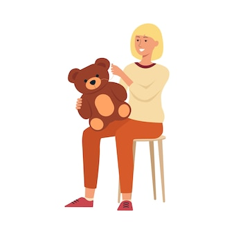 Woman sitting on chair and sewing teddy bear