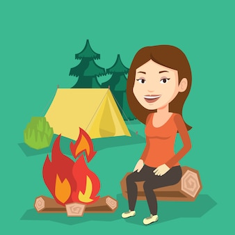 Woman sitting on log near campfire in the camping.