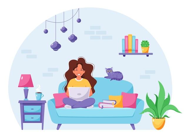 여자는 소파에 앉아 노트북에서 일하고. 프리랜서, 홈 오피스