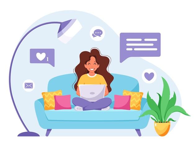 ソファに座ってラップトップで作業している女性
