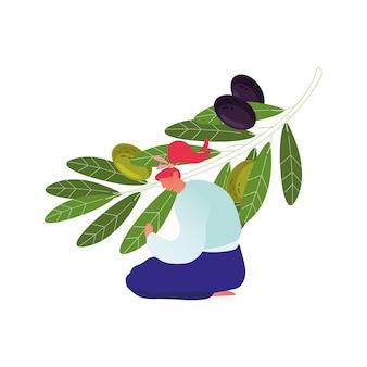 Женщина, сидящая на земле, ухаживает за оливковой ветвью с зелеными и черными ягодами и листьями