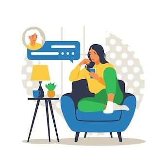電話でソファに座っている女性